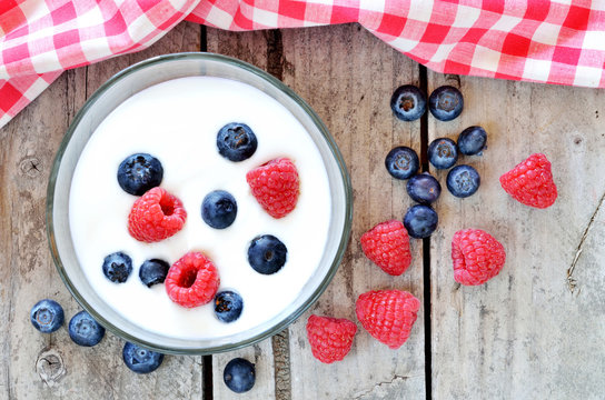 White yogurt in a bowl with blueberries and raspberries on wooden table