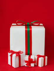 White gifts boxes with ribbon on red background