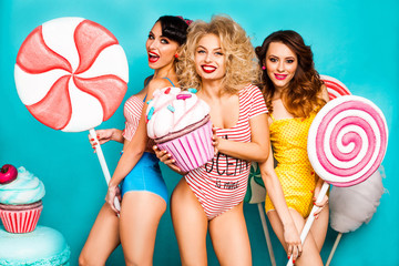Three young ladies are cool, keep on turquoise background Huge Cake and candy, laugh, crazy emotions, perfect make-up and hairstyles, trendy Pin-up girl, bright body, yellow, striped, red lips fashion