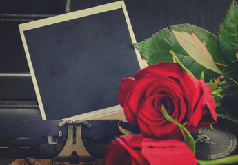instant phoro with red rose flowers on vintage typewriter , retro toned