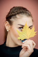 Girl with autumn leaf on her eye, vintage film effect