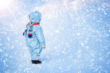 Boy in winter clothes at snowfall