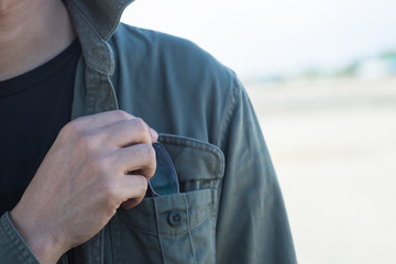 Male's hand with glasses in shirt pocket