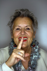it is christmas time! smiling middle aged woman with x-mas decoration holding finger on mouth and looking at camera while standing on white background