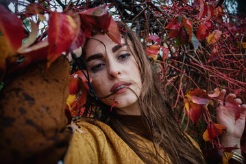 Tragic and dramatic portrait of a girl among the autumn leaves with melted makeup and wet hair