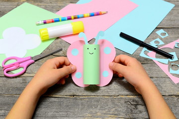 Child holding paper butterfly crafts in hands. Child shows a fun paper crafts. Stationery on an old wooden table. Preschool and kindergarten summer paper art. Easy diy for kids