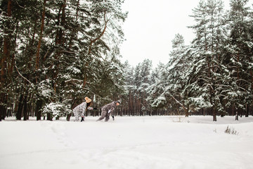 Winter concept, couple in animals costumes running in the snowy winter pine forest