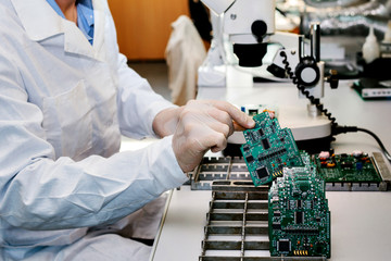Microchip production factory. Technological process. Assembling the board. Chip. Professional. Technician. Computer expert. Manufacturing. Engineering.