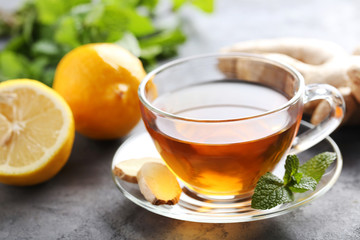 Cup of tea with ginger root and lemon on grey wooden table