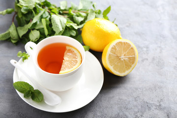 Cup of tea with mint and lemon on grey wooden table