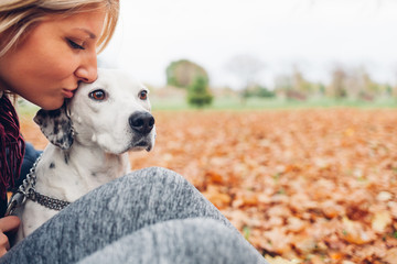 Happy owner woman kissing dog