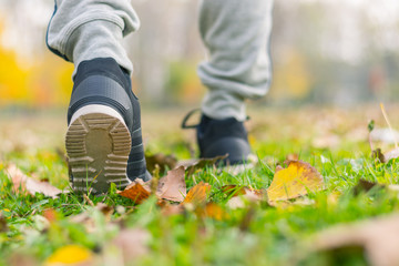 Young man running outdoors in a autumn forest on a cold fall/winter day, lifestyle and healthy concept