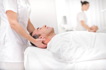 Male client enjoying facial treatment at spa