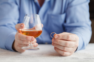 Sad man is holding a wedding ring near the glass of alcoholic be