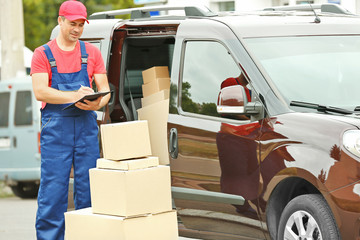 Delivery concept. Postman with parcels near a car