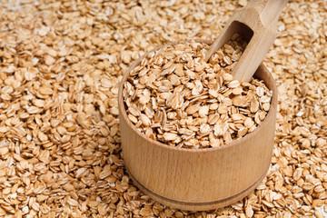 Background of oats in wooden bowl and scoop. Healthy food. Close up, top view, high resolution product