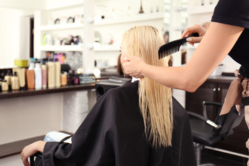Hairdresser combing blonde's hair at salon