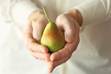 Senior man holding fresh pear