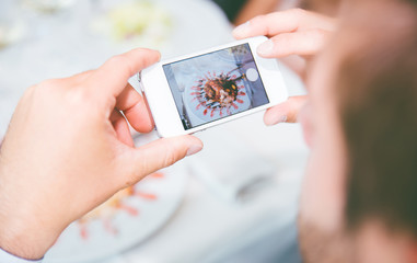 Man photographing food with smart phone