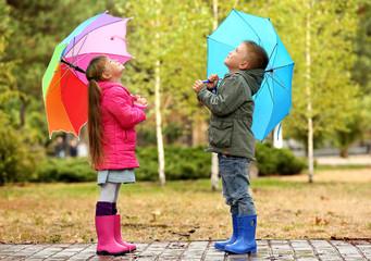 Cute children with umbrellas in park