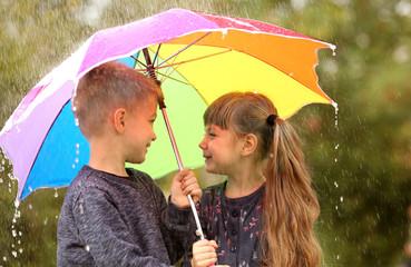 Portrait of cute children with umbrella in rain