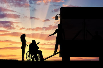 Disabled in wheelchair nurse helping to climb ramp in bus sunset