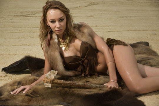 Prehistoric woman with the stone axe is sitting on the fur