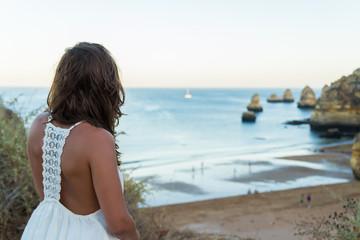 Girl sitting backwards at Donna Anna Beach, Portugal