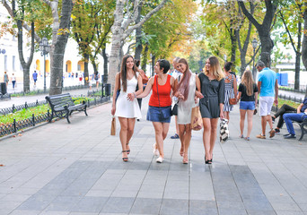 Walk four beautiful cheerful girls after shopping.