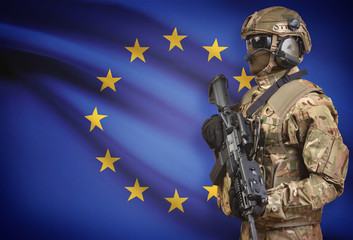 Soldier in helmet holding machine gun with flag on background series - European Union