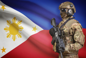 Soldier in helmet holding machine gun with flag on background series - Philippines