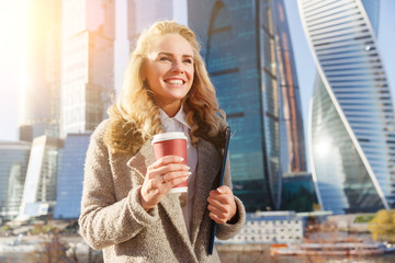 Happy blonde woman with bright smile on warm autumn day