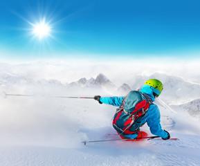 Freeride skier on piste running downhill