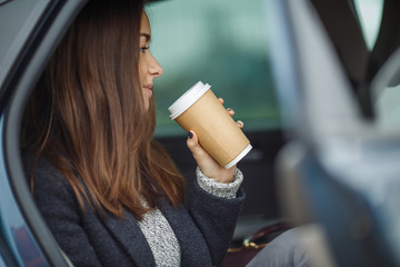 Beautiful woman with long brown hair drinking coffee in car