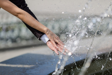 Hands of newly wedded under running water