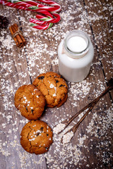 Homemade oatmeal cookies with nuts, raisins, candy cane and bottle of milk on dark wooden background, closeup, selective focus
