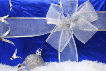 Gift in the blue box and silver Christmas ball. Close-up