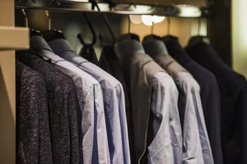 Men clothing on hangers in a fancy shoip