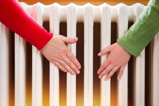 Two hands touch the radiator