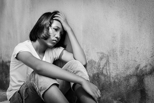 Concept teen proplem ,sad girl sitting alone black and white tone