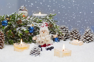 Christmas still life is with snow. Toy Santa Claus is sitting under a Christmas tree.