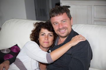 Confident middle aged couple relaxing in couch