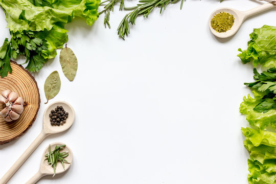 frame spices and fresh herbs on white table top view
