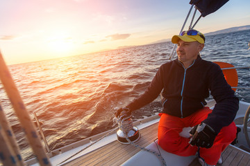 Man sits on yacht during sunset. Luxury sailing boats. Travel, vacation.