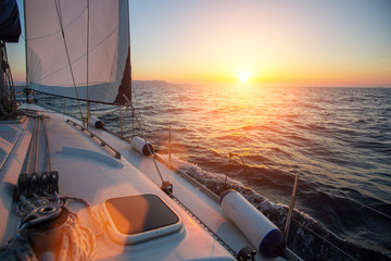 Wall Mural - Amazing sunset at sea shot of a luxery yacht boat. Sailing in the wind through the waves.