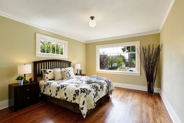 Cozy bedroom interior. Queen size bed with floral patterned bedding