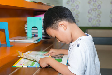 Cute little boy reading book in the library