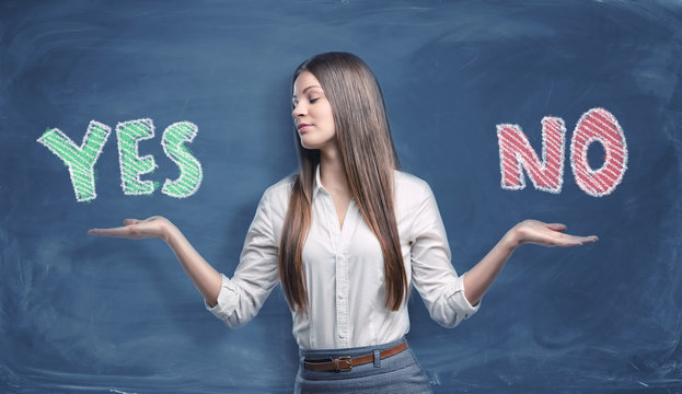 Beautiful businesswoman standing with open palms between big colorful words 'yes' and 'no' written on dark blue background.