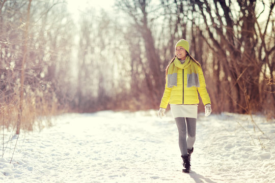 Winter happy woman walking in snow outdoors nature. Joyful young person relaxing on an outdoor walk activity in snowy forest landscape wearing warm yellow fashion outerwear jacket boots, scarf, hat.