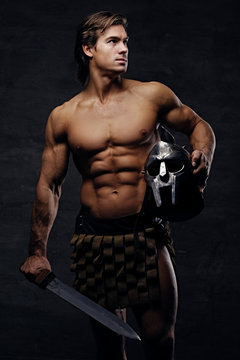 Portrait of shirtless muscular male holds silver gladiator helme